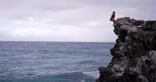 Caucasian woman doing back flip off cliff into ocean on Maui Royalty-free stock video