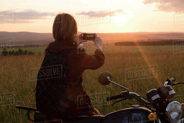 Caucasian woman with motorcycle in field photographing sunset Royalty-free stock photo