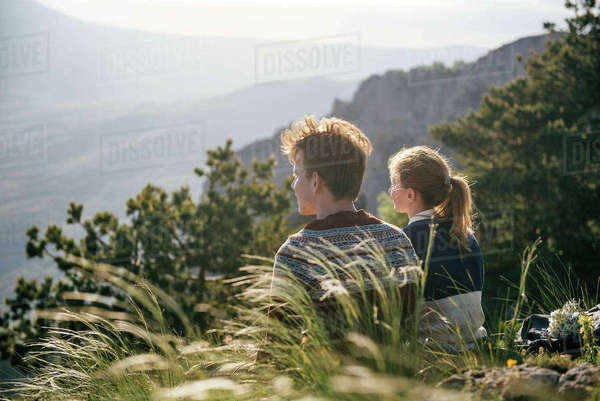 Caucasian couple sitting on hill admiring scenic view Royalty-free stock photo