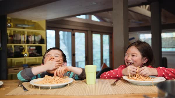 Messy brother and sister eating spaghetti Royalty-free stock video