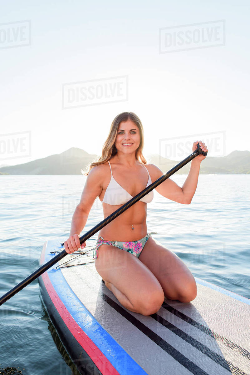 hispanic woman kneeling on paddleboard in river stock photo dissolve