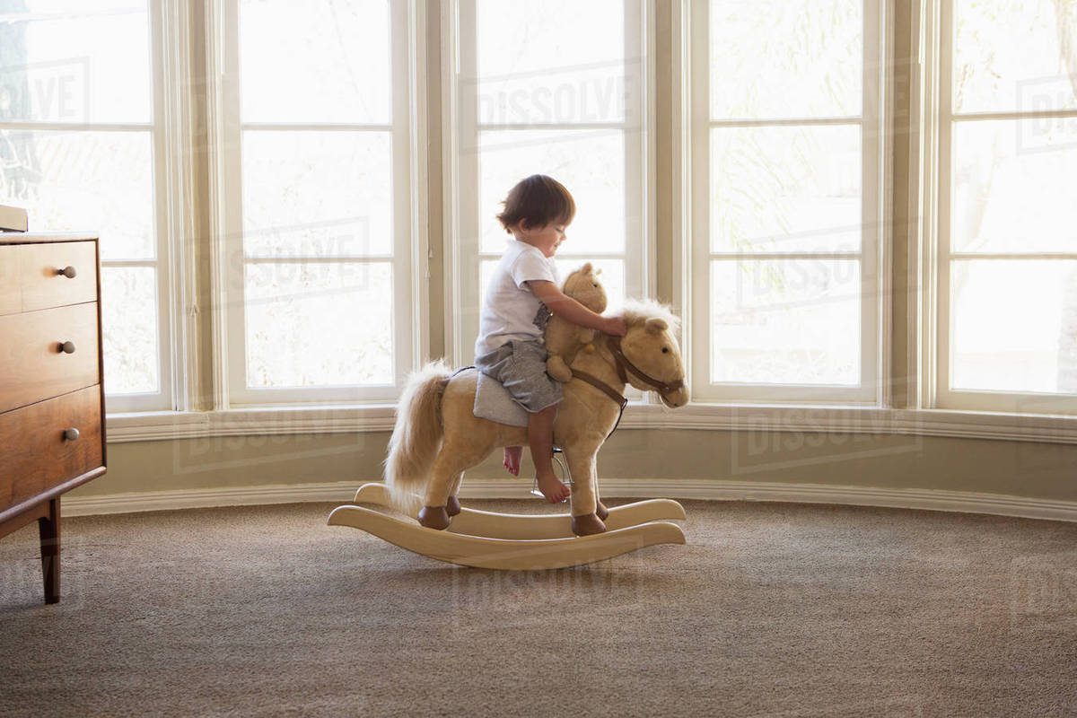 Mixed Race boy sitting on rocking horse near window Royalty-free stock photo