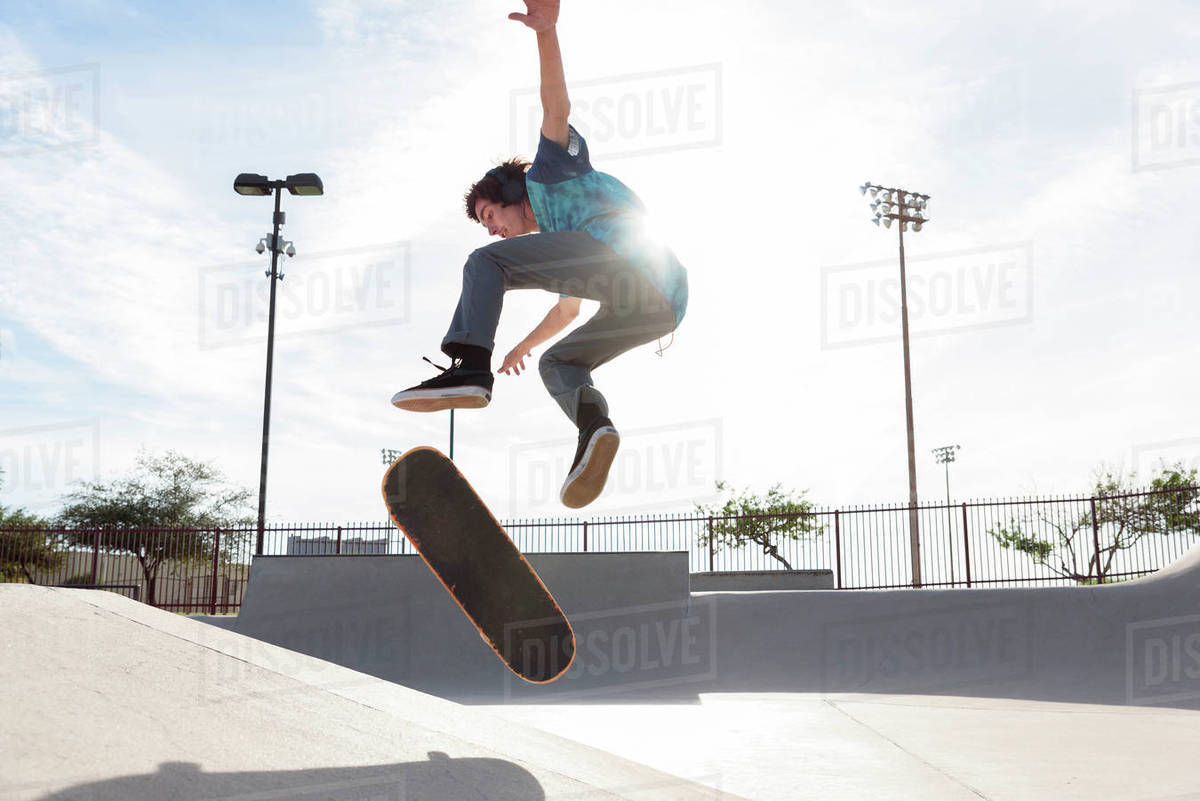 Hispanic man performing mid-air trick on skateboard Royalty-free stock photo