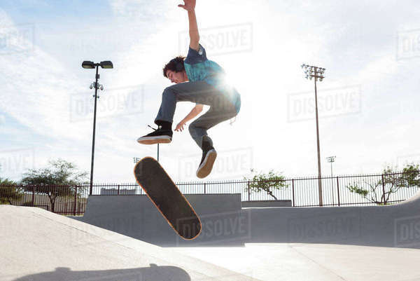 Hispanic man performing mid-air trick on skateboard Royalty-free stock photo