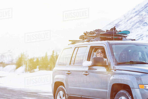 Friends driving in car with snowboards in winter Royalty-free stock photo