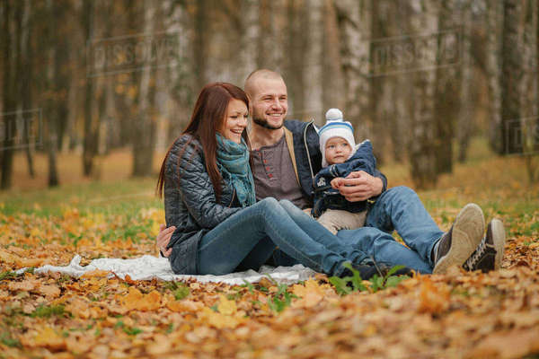 Middle Eastern couple sitting in park with baby son in autumn Royalty-free stock photo