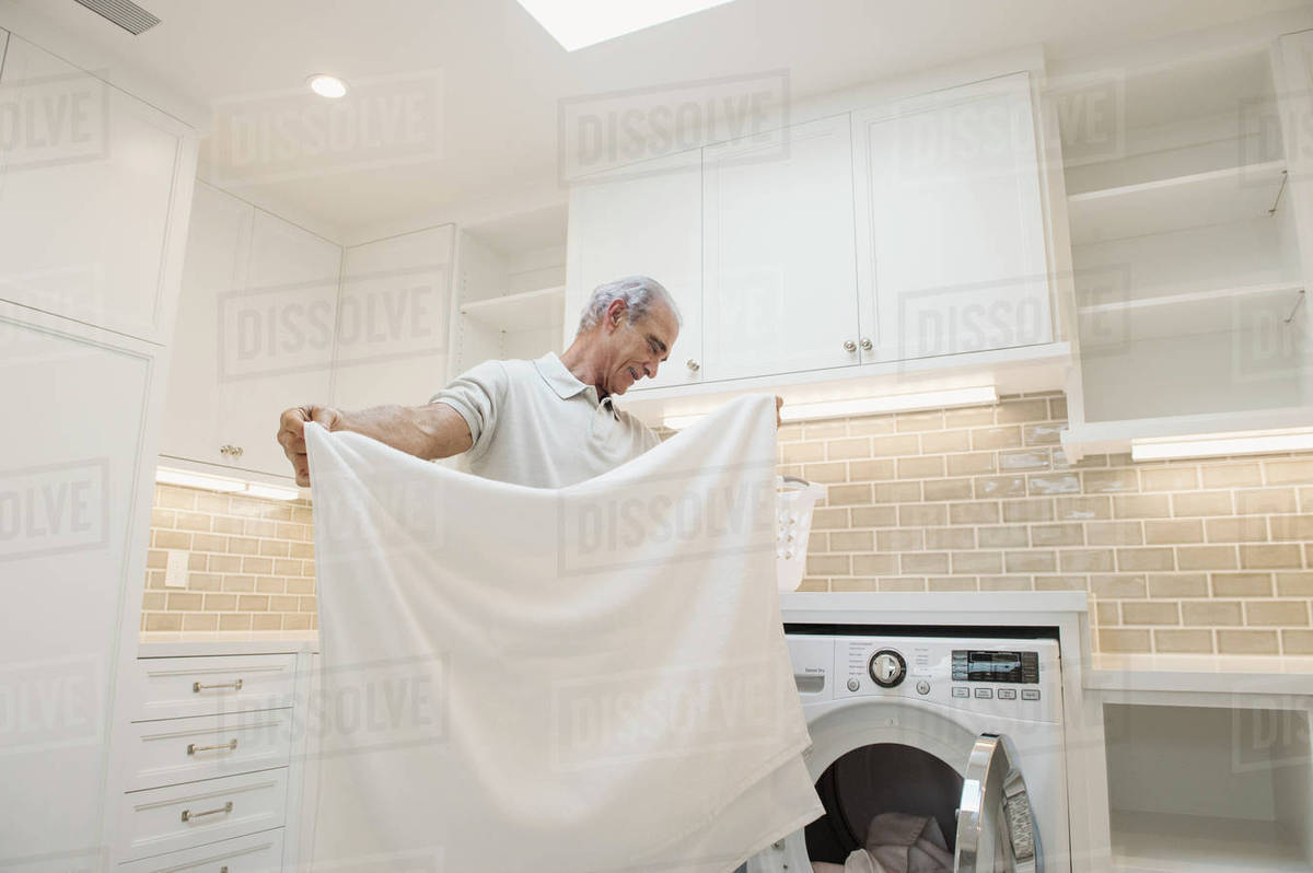 Caucasian man folding towel in modern laundry room - Stock Photo ...
