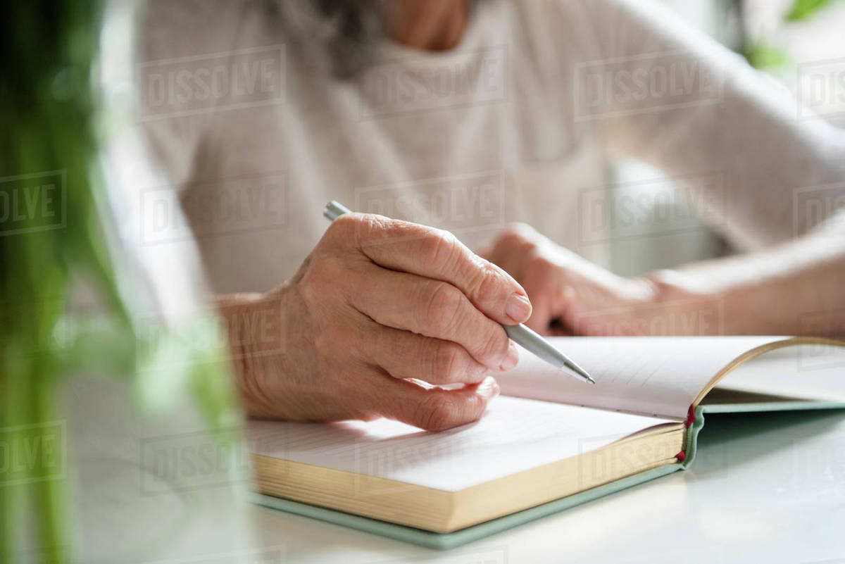 hands of older woman writing in journal - stock photo - dissolve