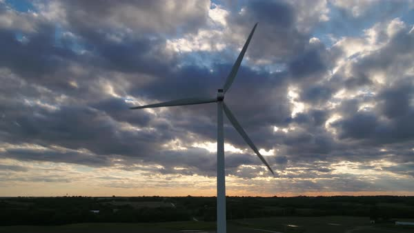Giant wind turbine turning at sunset under dramatic sky Royalty-free stock video
