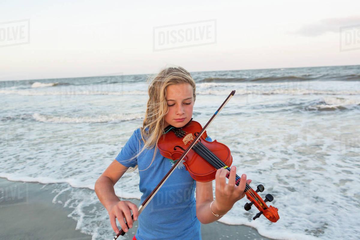 Caucasian girl playing violin at beach stock photo
