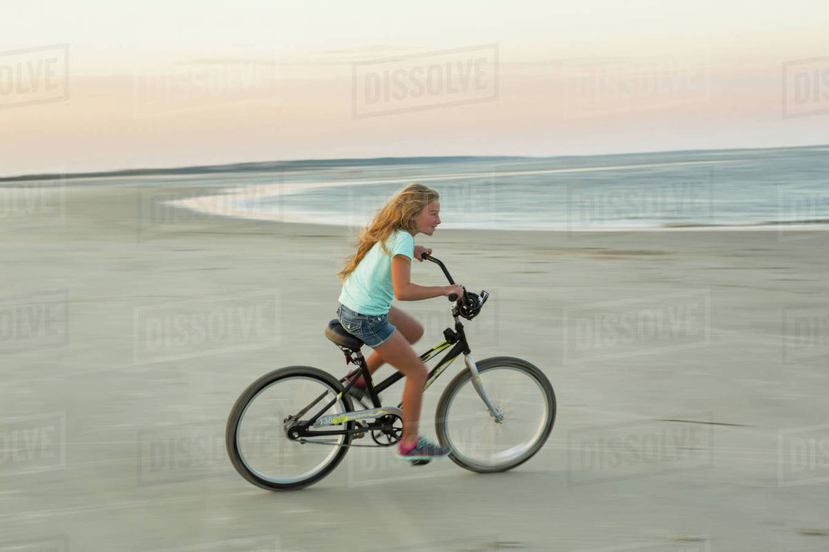 Caucasian Riding Bicycle On Beach