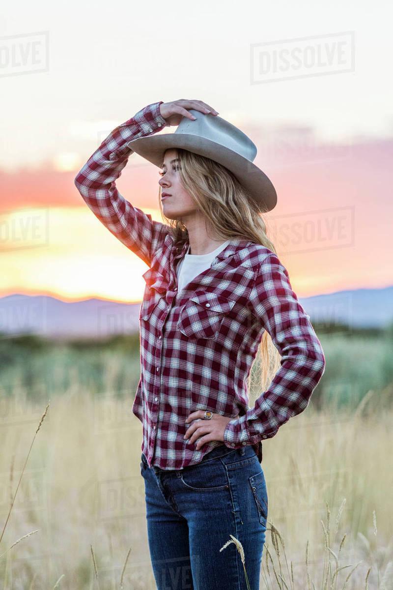 Caucasian teenage girl wearing cowboy hat at sunset - Stock Photo ... 5bb7c6a927e