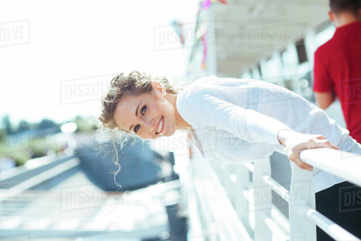 smiling caucasian woman leaning over railing stock photo dissolve