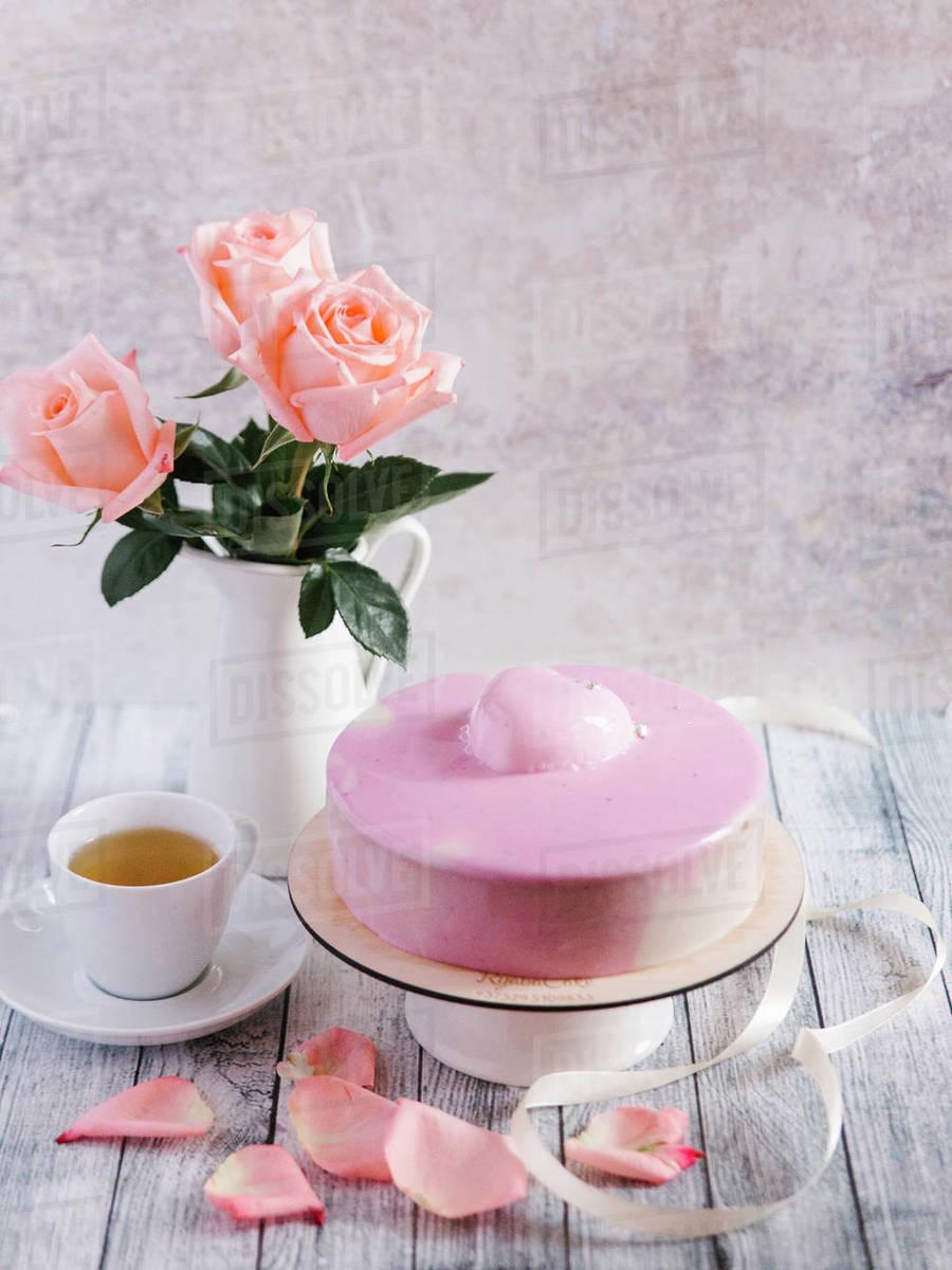 Pink Cake With Tea Near Vase Of Flowers Stock Photo Dissolve