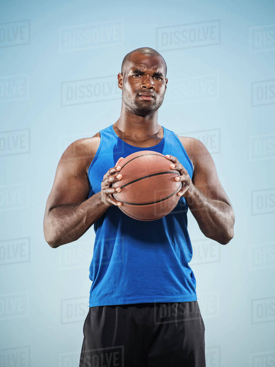 portrait of serious black man holding basketball stock photo
