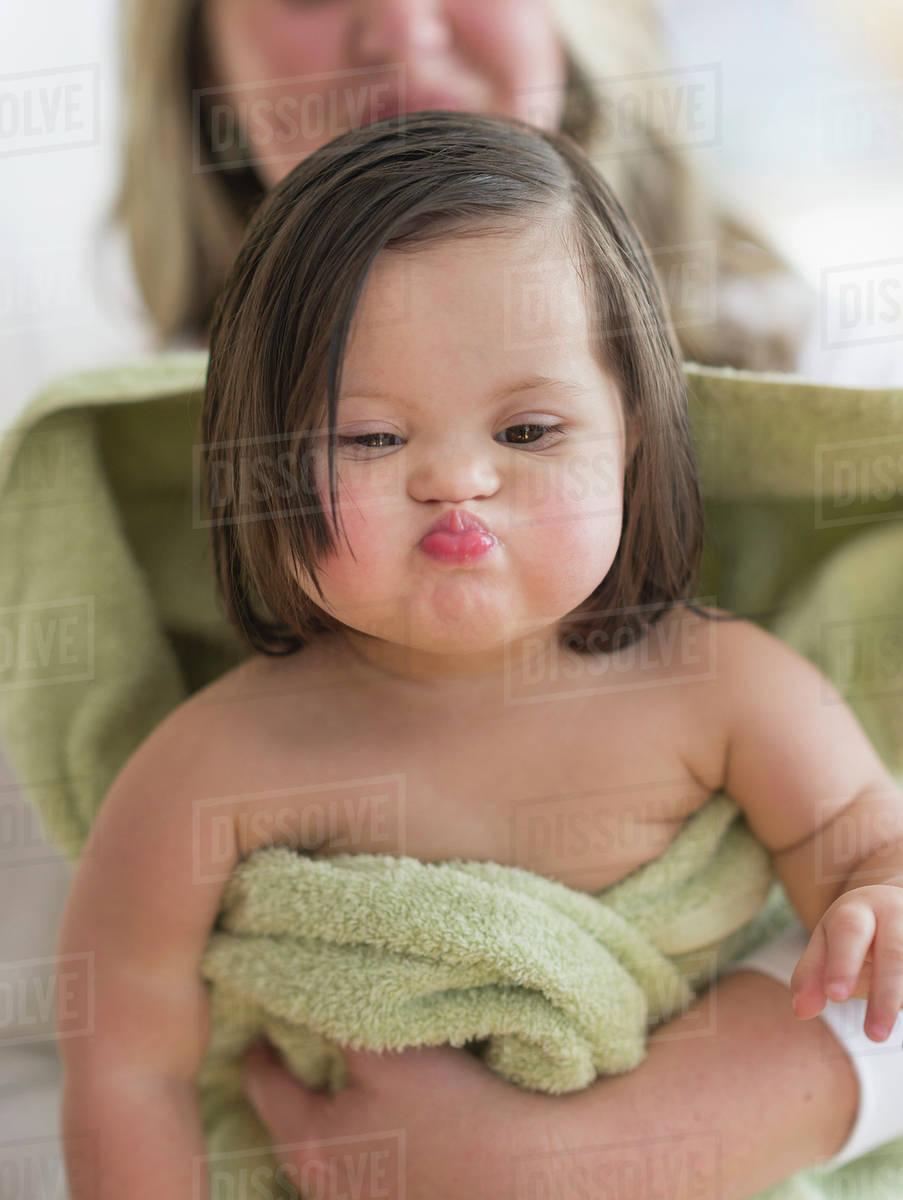 Hispanic toddler making faces after bath - Stock Photo - Dissolve