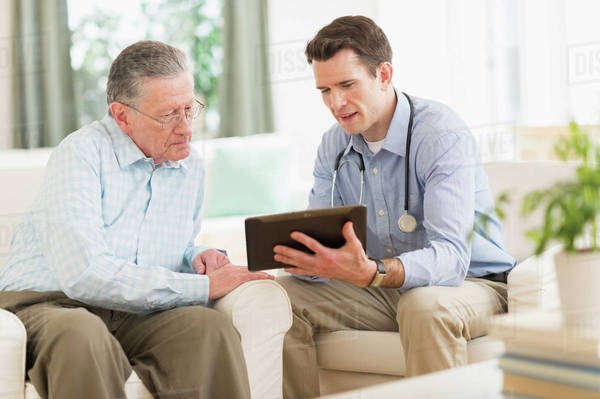 Caucasian doctor and patient using digital tablet at home Royalty-free stock photo