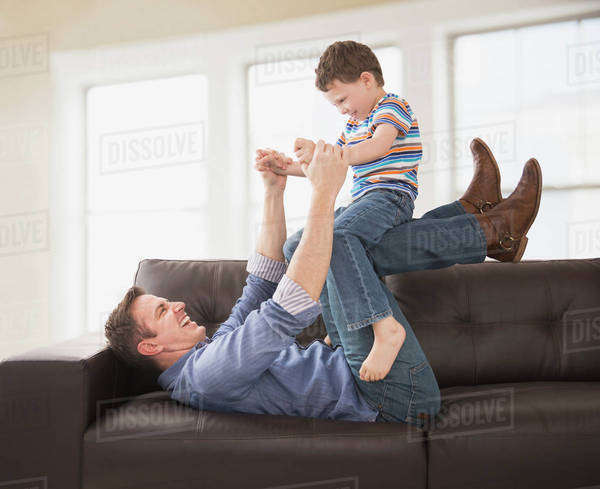 Caucasian father and son playing on sofa Royalty-free stock photo