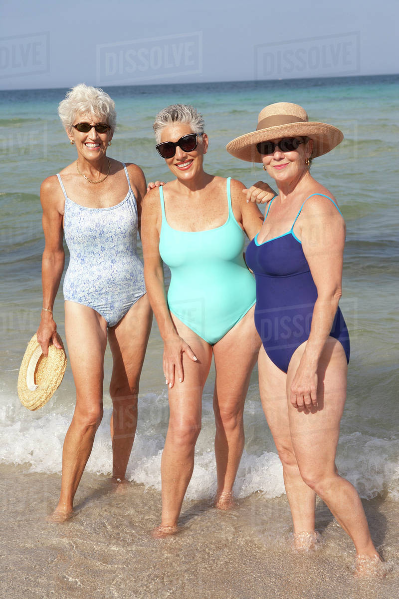 Senior women standing in waves on beach Royalty-free stock photo