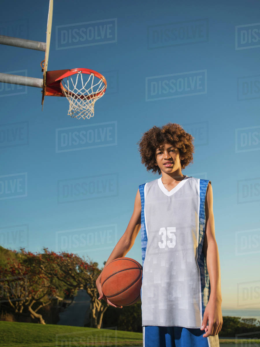 black teenage boy holding basketball on court stock photo dissolve