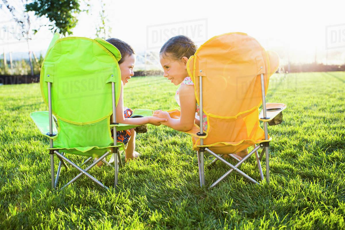 Swell Caucasian Children Relaxing In Lawn Chairs In Backyard D145 38 211 Machost Co Dining Chair Design Ideas Machostcouk