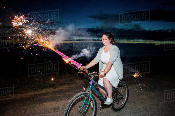 Woman holding fireworks on bicycle at night Royalty-free stock photo