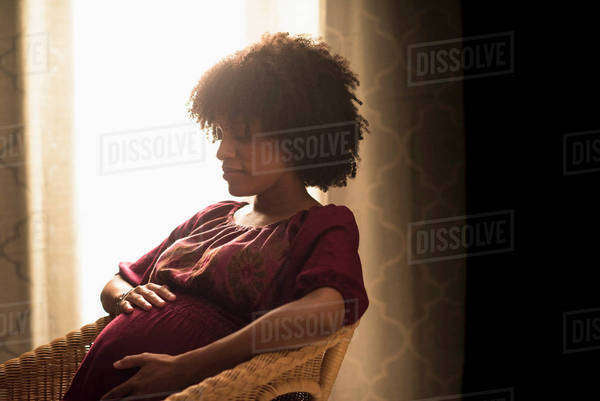 Pregnant African American mother holding her stomach Royalty-free stock photo