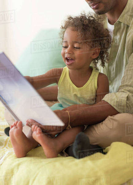 Father and daughter reading book on bed Royalty-free stock photo