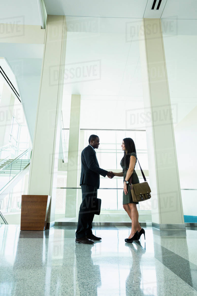 Business people shaking hands in office hallway Royalty-free stock photo