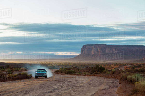 Car driving on dirt road in desert, Monument Valley, Utah, United States Royalty-free stock photo