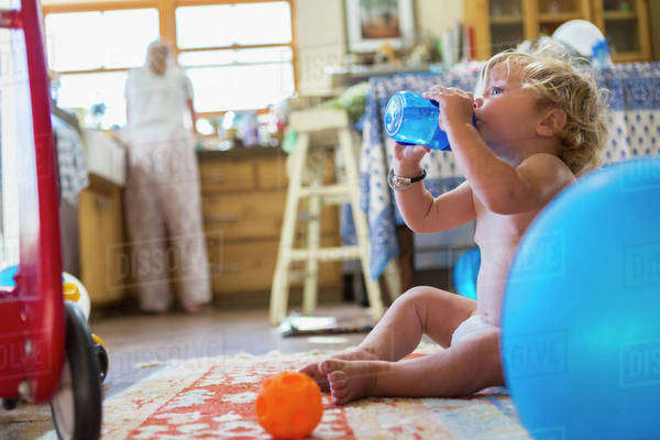 Caucasian baby boy drinking water in kitchen Royalty-free stock photo