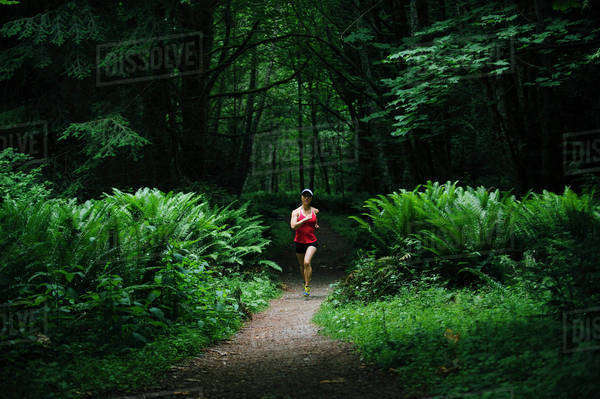 Korean woman running in lush forest Royalty-free stock photo
