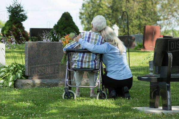 Caucasian mother and daughter visiting grave in cemetery Royalty-free stock photo