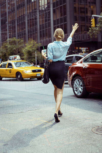Caucasian woman hailing taxi in urban street Royalty-free stock photo