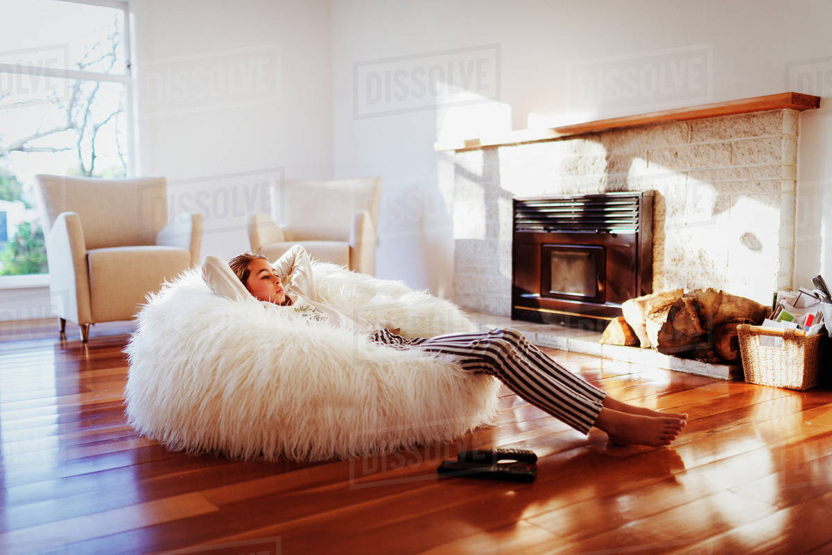 Mixed race girl relaxing in beanbag chair in living room stock photo