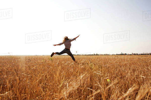 Caucasian woman jumping for joy in rural field Royalty-free stock photo