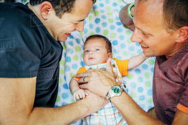 Caucasian gay couple cuddling baby boy Royalty-free stock photo