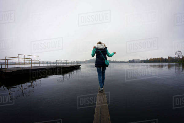 Caucasian woman balancing on dock over still lake Royalty-free stock photo