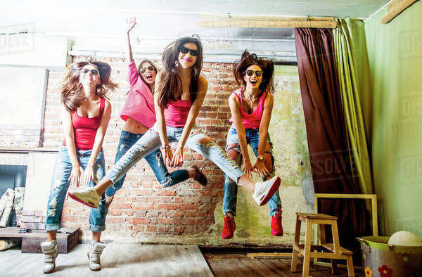 Caucasian women jumping in living room Royalty-free stock photo