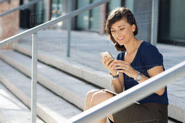 Caucasian businesswoman using cell phone on staircase Royalty-free stock photo