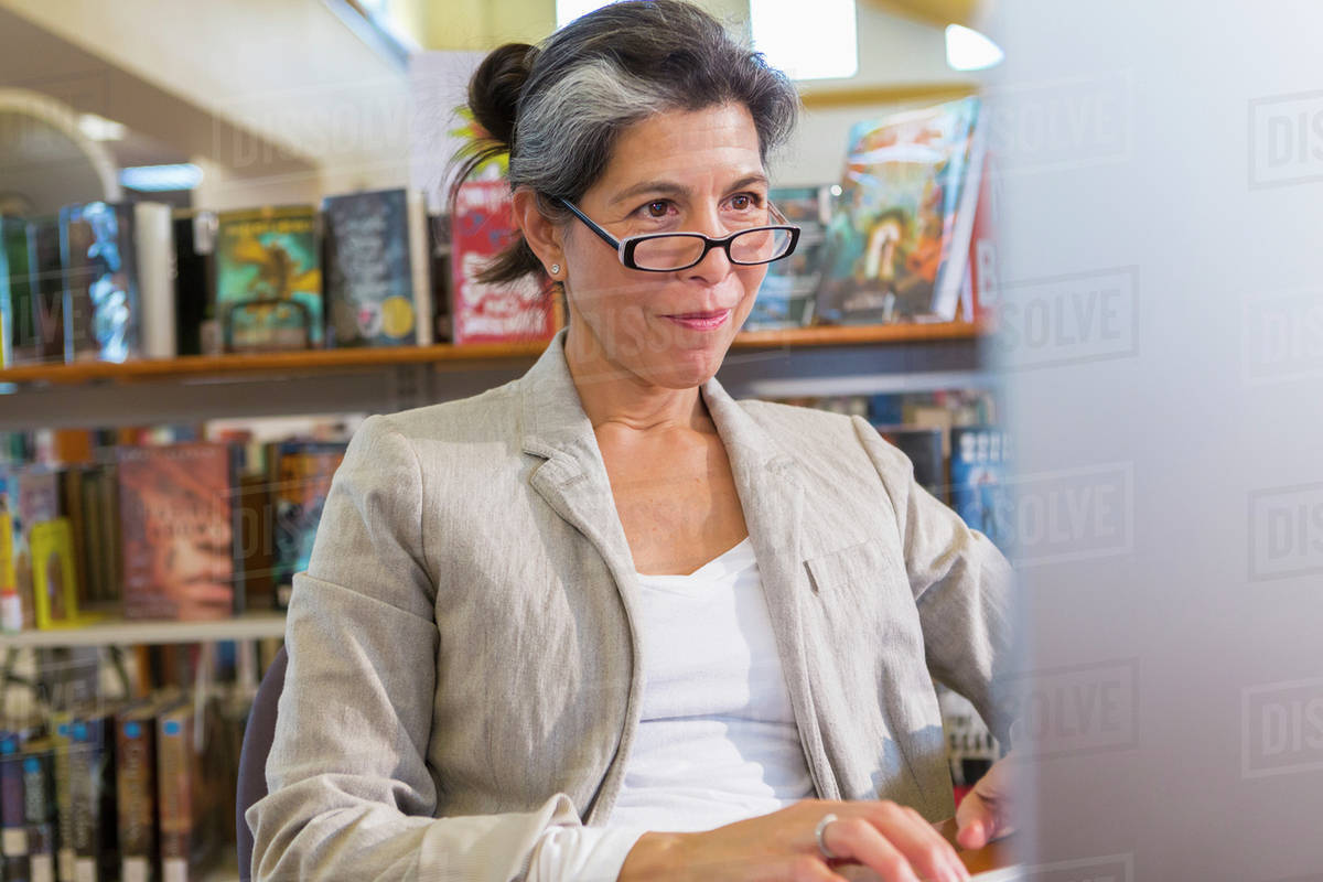Older Hispanic woman using computer in library Royalty-free stock photo