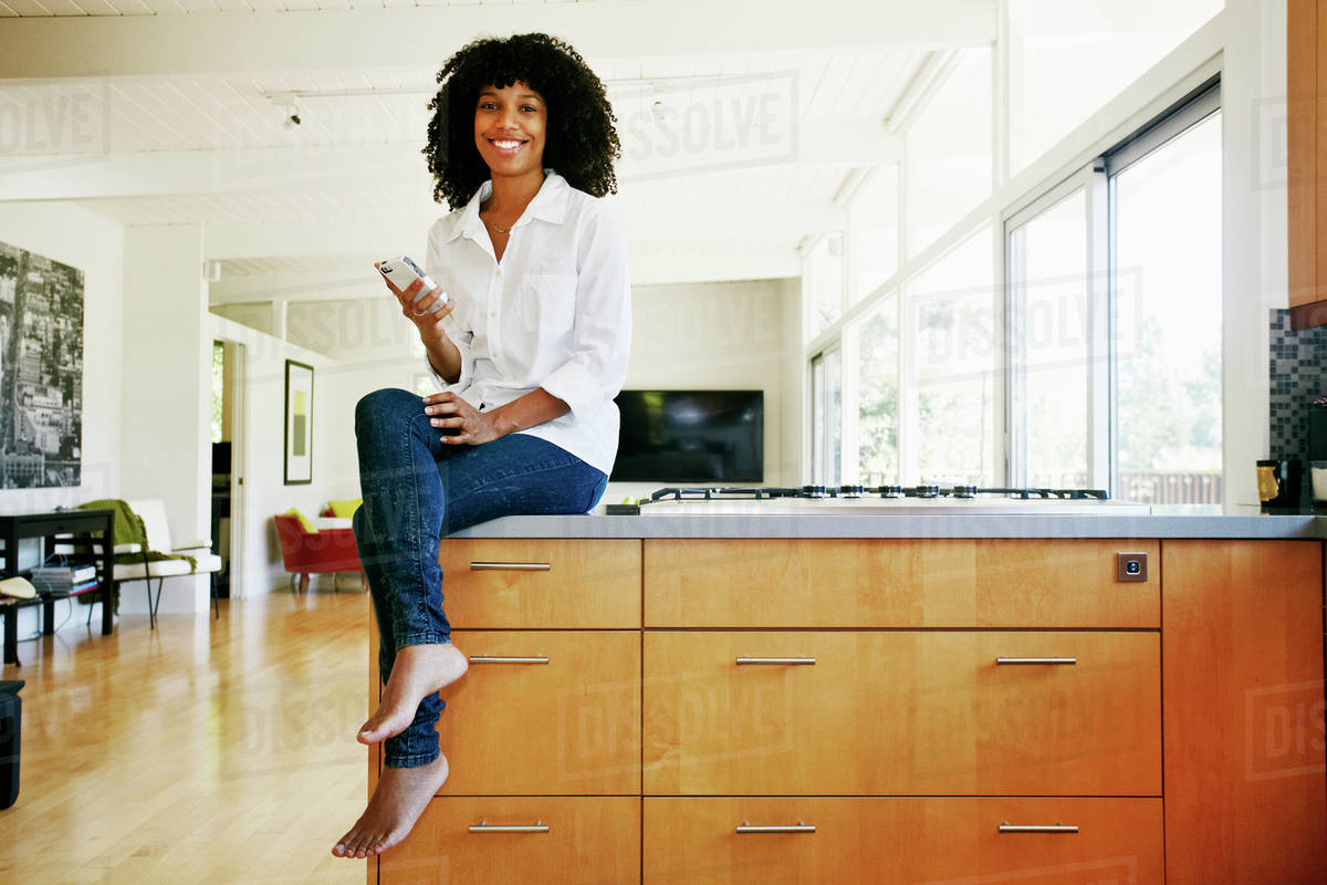 Mixed race woman using cell phone in domestic kitchen Royalty-free stock photo
