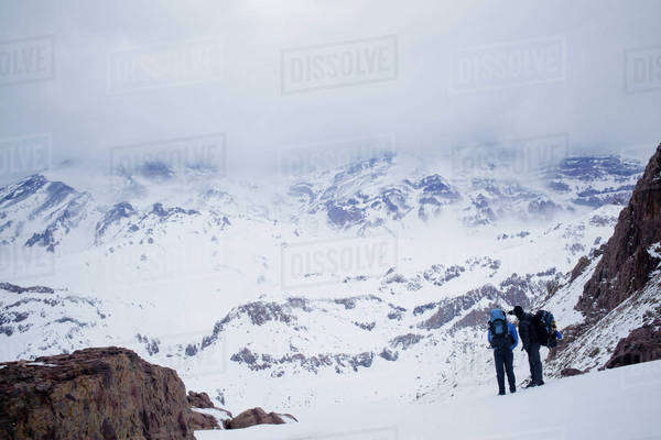 Hispanic hikers admiring snowy scenic mountains Royalty-free stock photo