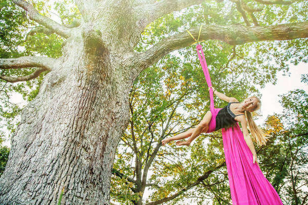 Acrobatic Caucasian girl hanging on fabric under tree Royalty-free stock photo