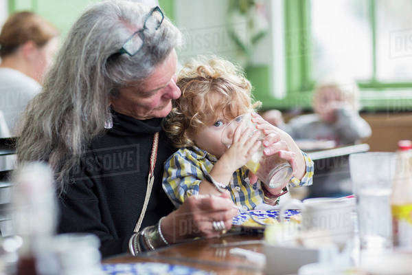 Caucasian grandmother and grandson eating dinner in restaurant Royalty-free stock photo