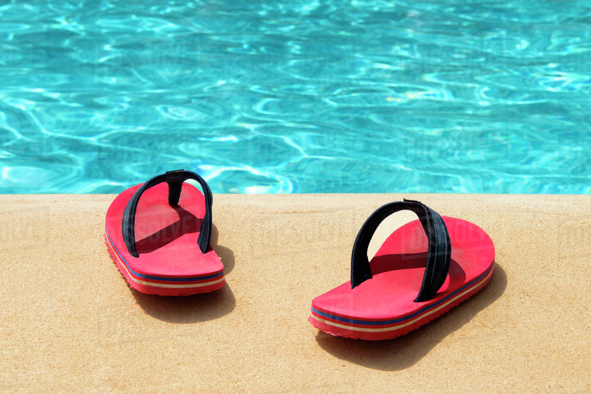 487d89eab64759 A pair of red flip flops at the swimming pool - Stock Photo - Dissolve