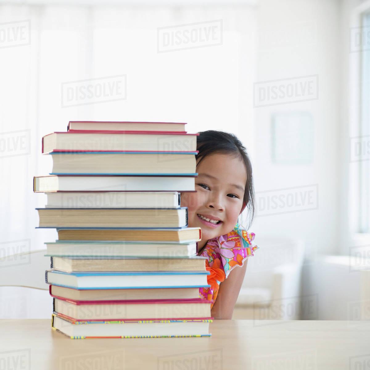 Korean girl peeking from behind stack of books stock photo
