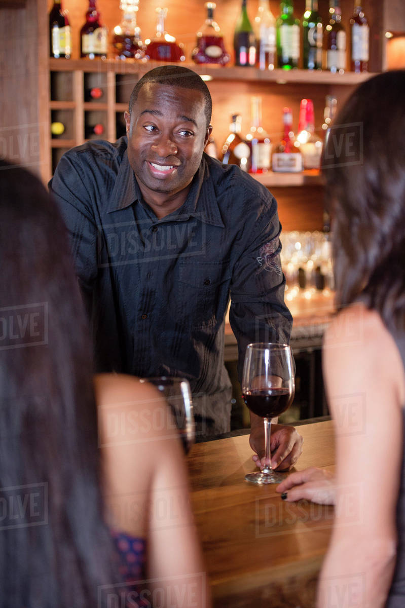 African American bartender serving customers - Stock Photo - Dissolve