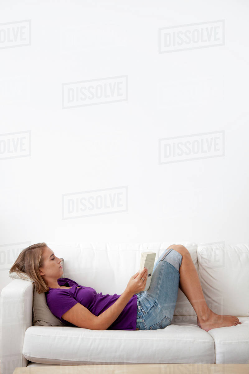 Caucasian Woman Laying On Sofa Reading Book