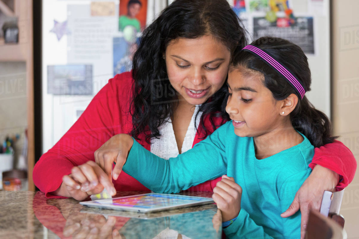 Indian mother and daughter using digital tablet at counter stock photo
